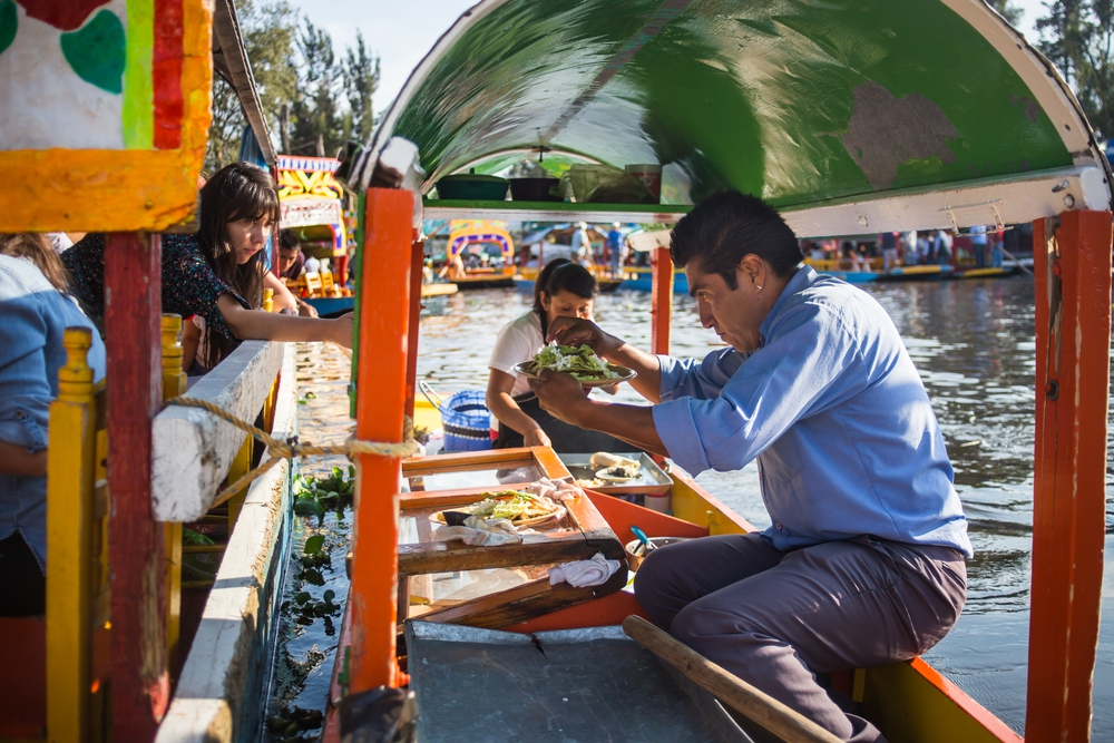 Floating fiesta in Mexico. A colourful boat cruise in the district of Xochimilco